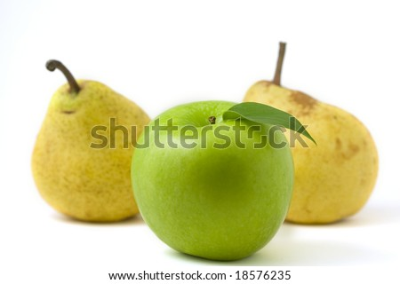 Green apple with leaf in front of two pears isolated on white