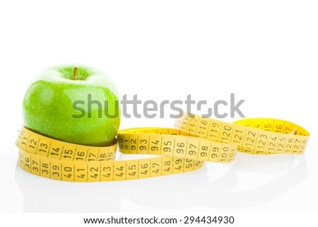 green apple with measure tape. studio shot - stock photo
