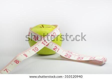 Green apple with measurement tape isolated on white background