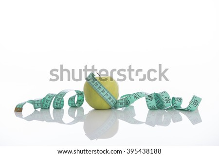 Green apple with measuring tape isolated on white - stock photo