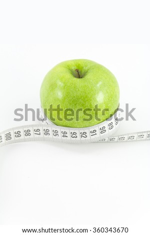 Green apple with measuring tape on white background. Green apple with measurement isolated on white. Measuring tape wrapped around a green apple as a symbol of diet. Healthy food concept.  - stock photo