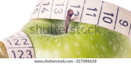 green apple with measuring tape over a white background / healthy living - stock photo