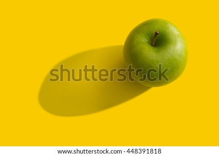 Green apple with shadow over yellow background