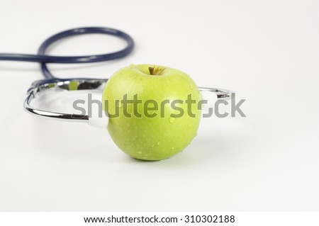 Green apple with stethoscope and measurement tape
