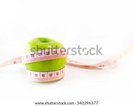 Green apple wrapped around with measure tape