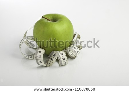 Green apple wrapped with tape-measure