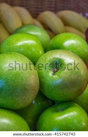 Green apples and bananas in a basket on a table on a self service breakfast counter in a hotel
