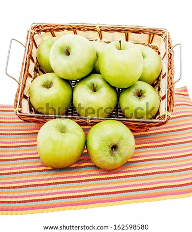 Green apples in a basket and a placemat - stock photo