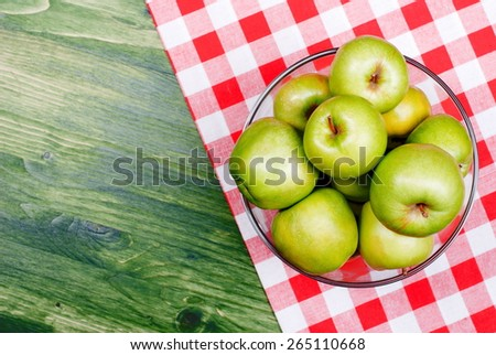 Green apples in a large glass bowl on a table with a checkered napkin, top view - stock photo
