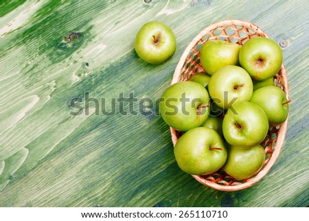 Green apples in a wicker basket on a green table, top view  - stock photo
