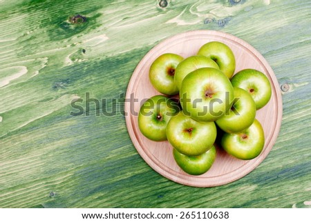 Green apples stacked pyramid on a cutting board, top view  - stock photo