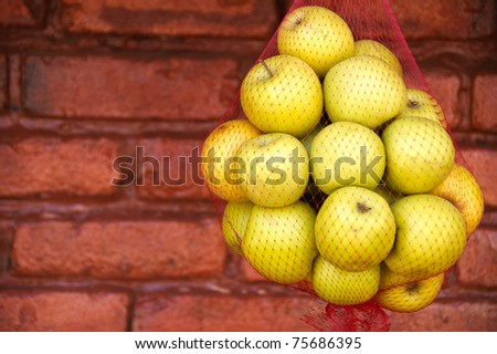 green apples suspended in a red net bag - stock photo