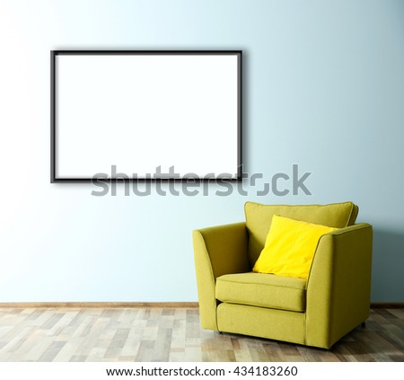 Green armchair and empty picture frame on blue wall background - stock photo