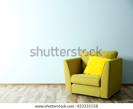 Green armchair on blue wall background - stock photo