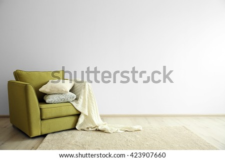 Green armchair on light wall background - stock photo