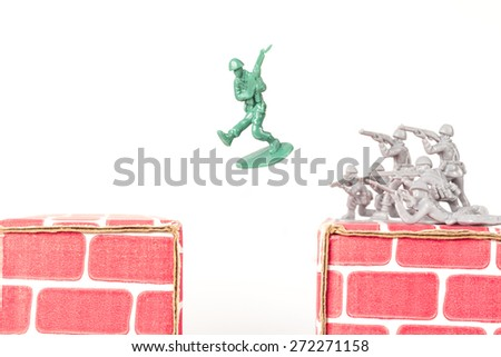 Green army man jumps ravine to escape gray army - stock photo