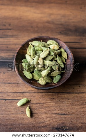 Green aromatic cardamom in a wooden bowl, selective focus - stock photo