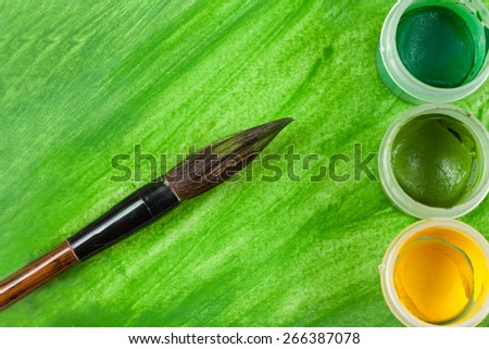 Green artistic watercolor painting  with artist's paintbrush tool and three cups with different paint colors - stock photo