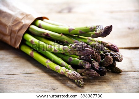 green asparagus bunch in brown paper on a rustic wooden board, closeup with selected focus and narrow depth of field - stock photo