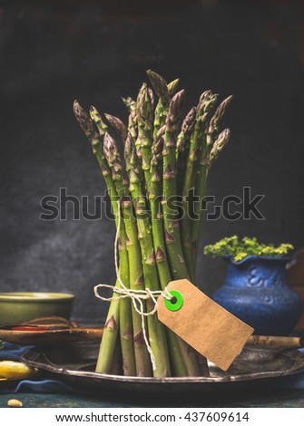 Green asparagus bunch with blank tag standing on dark kitchen table - stock photo