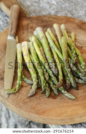 Green asparagus on a wooden chopping board - stock photo