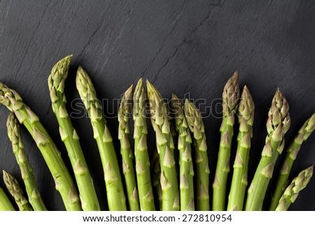 Green Asparagus on black stone background - stock photo