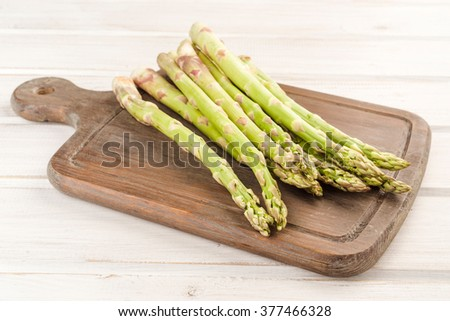 green asparagus on white wood listed - stock photo