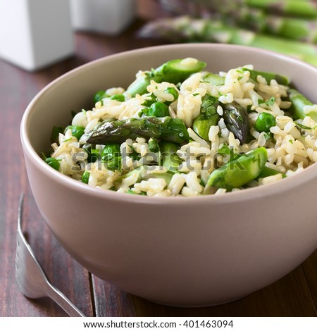 Green asparagus, pea, parsley and brown rice risotto served in bowl, photographed on dark wood with natural light (Selective Focus, Focus on the middle of the dish)