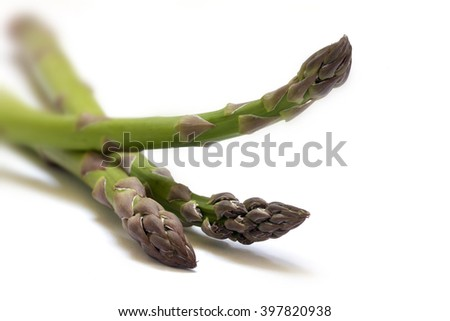 green asparagus, three spears in a closeup shot, isolated with shadows on a white background, selected focus and very narrow depth of field - stock photo