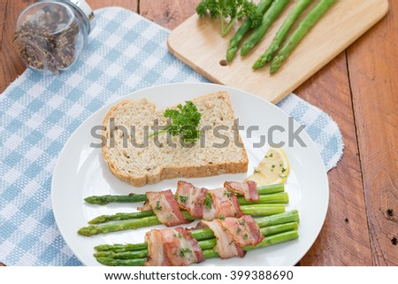 Green asparagus with bread and butter on a white plate.  - stock photo