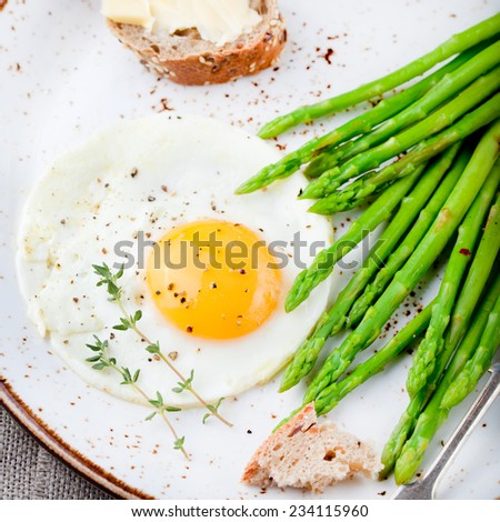 Green asparagus with fried egg and bread with butter on a white plate. - stock photo