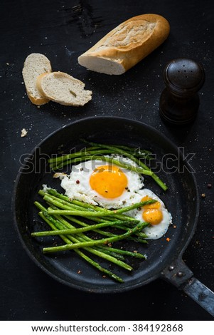 Green asparagus with fried sunny side up egg in skillet and fresh baguette on black background. Top view, vertical composition - stock photo