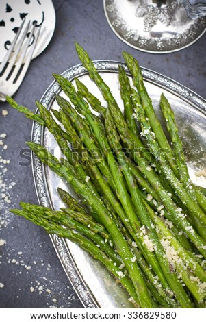 Green asparagus with parmesan cheese on silver plate - stock photo