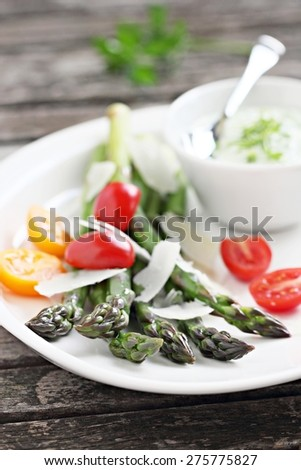 Green asparagus with tomatoes,parmesan and herbs dip.Selective focus.