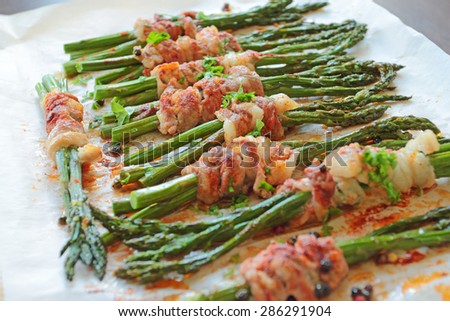 Green asparagus wrapped in bacon - stock photo