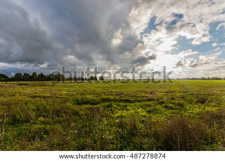 Green autumn fields with massive stormy clouds. Nature landscape.