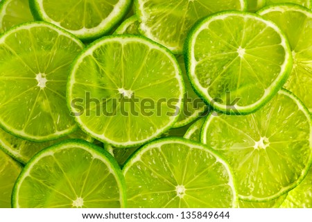 Green background with citrus-fruit of lime slices - stock photo
