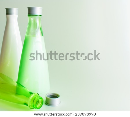 Green background with cosmetic bottles, copy space - stock photo