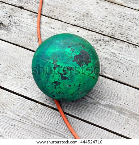 Green ball on a wharf with orange wire - stock photo