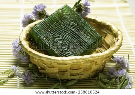 green bar soap in a basket with flowers - stock photo