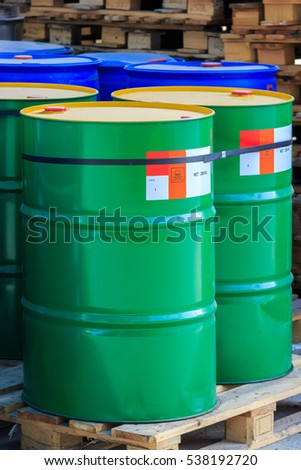 Green barrels with label poison standing on wooden pallets on a chemical plant