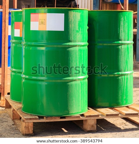 Green barrels with label standing on wooden pallets on a chemical plant - stock photo
