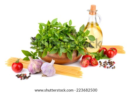 Green basil, olive oil, cherry tomatoes, garlic and yellow spaghetti on white background - stock photo
