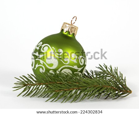 Green bauble on the twig of the spruce - stock photo