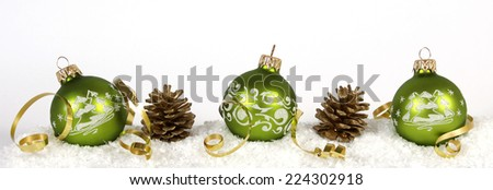 Green baubles and cones on the snow - stock photo