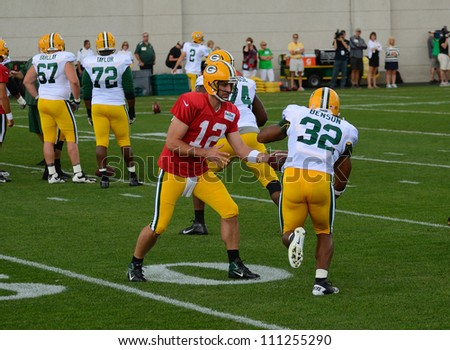 GREEN BAY, WI - AUGUST 19 : Green Bay Packers Quarterback Aaron Rodgers Hands Off the Football to Cedric Benson During Training Camp Practice on August 19, 2012 in Green Bay, WI - stock photo