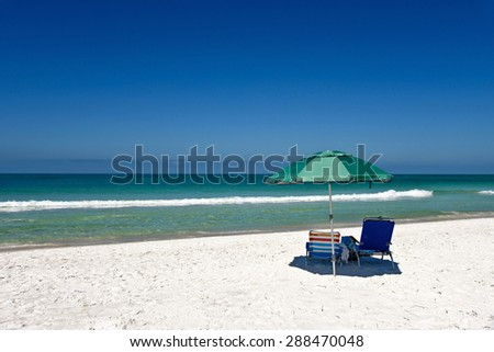 Green Beach Umbrella and Two Chairs on White Sandy Beach - stock photo