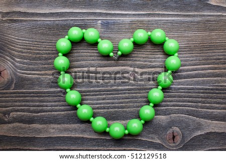 green beads on a wooden background