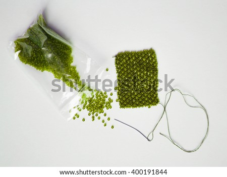 green beads package, woven beaded mesh and needle on white background