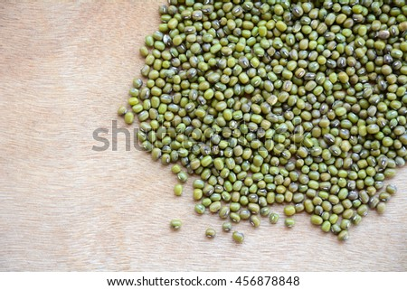 Green bean or mung bean seeds on a wooden floor.